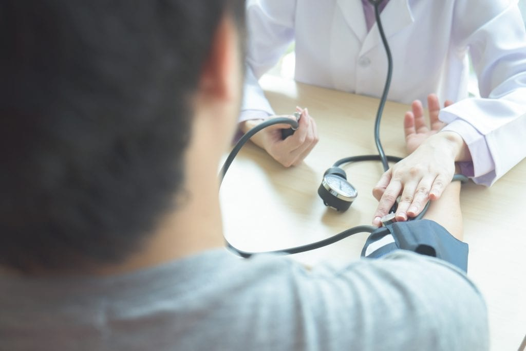Doctor checking patient arterial blood pressure
